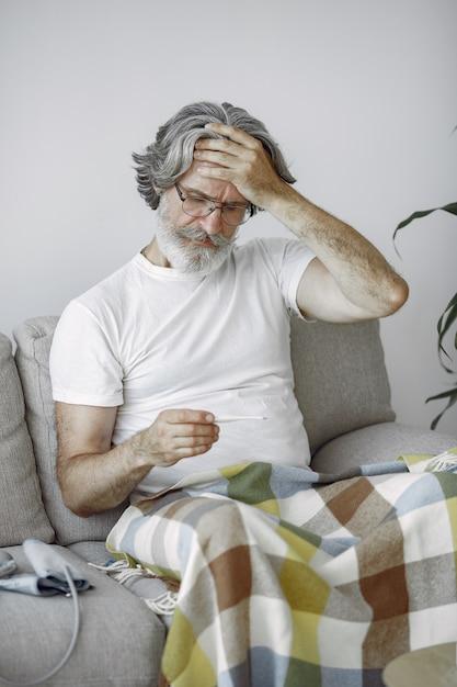 Senior Homme Seul Assis Sur Un Canapé. Homme Malade Recouvert De Plaid. Grangfather Avec Thermomètre. Photo gratuit