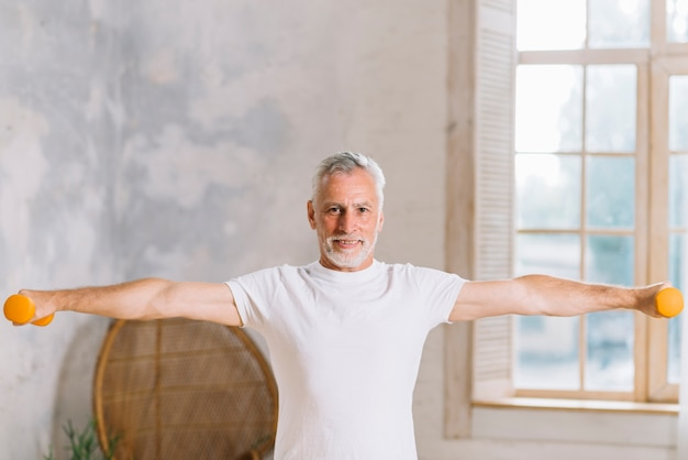 Senior homme souriant avec des haltères à la maison Photo gratuit