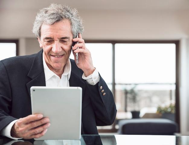 Senior homme souriant, parlant au téléphone mobile en regardant une tablette numérique sur le lieu de travail Photo gratuit