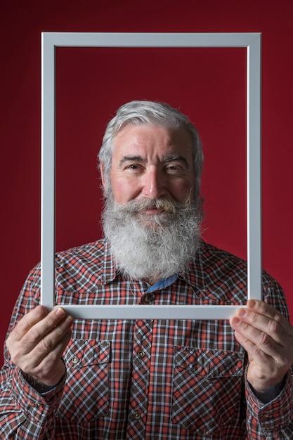 Senior homme souriant, tenant une bordure blanche sur fond coloré Photo gratuit