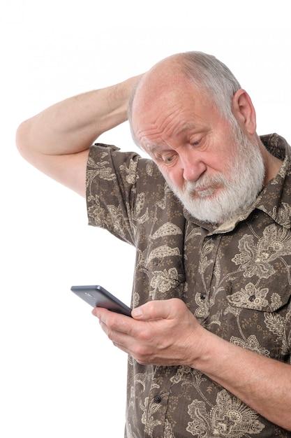 Senior homme surpris et confondu avec quelque chose au smartphone mobile, isolé sur blanc Photo Premium