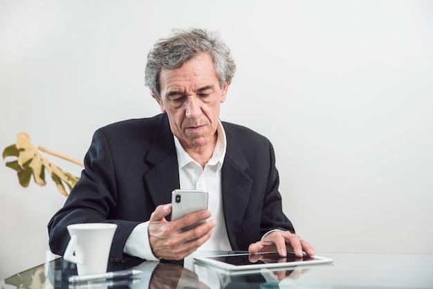 Senior homme avec tablette numérique en regardant téléphone mobile Photo gratuit