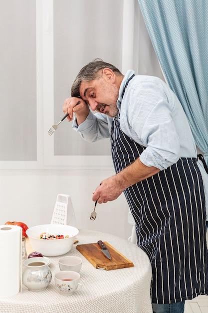 Senior homme tenant des fourchettes pour la salade Photo gratuit