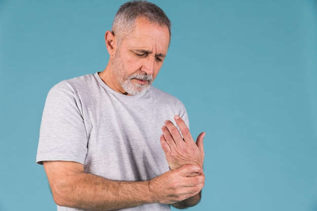 Senior homme tenant son poignet douloureux Photo gratuit