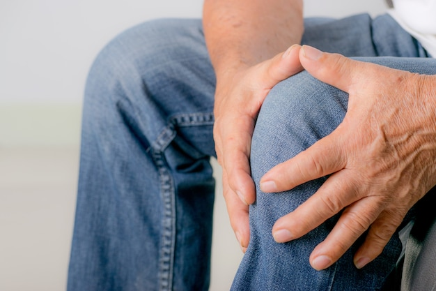 Senior homme toucher son genou par la douleur de l'arthrite. journée mondiale des personnes âgées. Photo Premium
