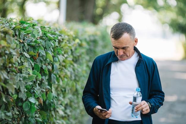 Senior homme vérifiant mobile en plein air Photo gratuit