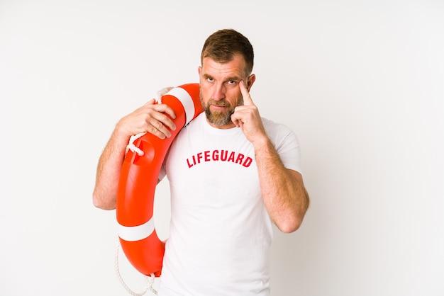 Senior Lifeguard Man Isolated On White Wall Pointant Le Temple Avec Le Doigt, Pensant, Concentré Sur Une Tâche. Photo Premium