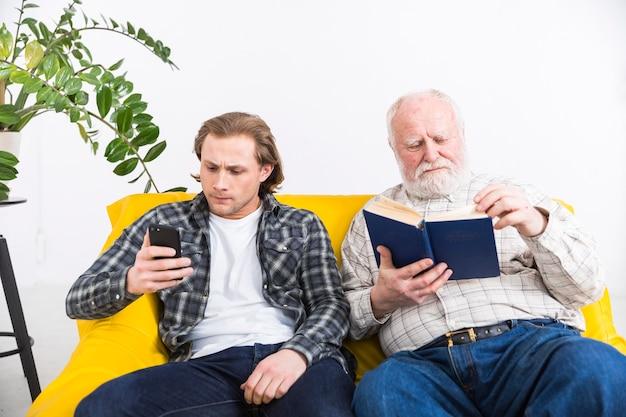 Senior père et fils adulte se détendre séparément Photo gratuit