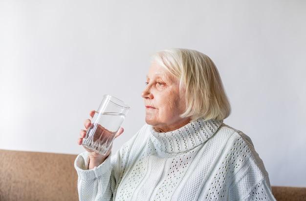 Senior Senior Tenant Un Verre D'eau Photo Premium