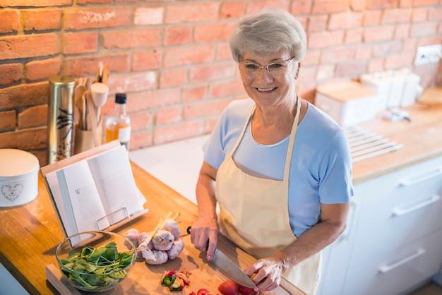 Senior Woman Couper Les Légumes De Saison Photo gratuit