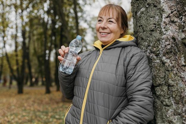 Senior Woman Eau Potable Après Avoir Travaillé Dans La Nature Photo gratuit