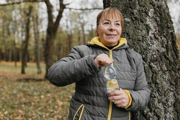 Senior Woman Eau Potable Après Avoir Travaillé à L'extérieur Photo gratuit