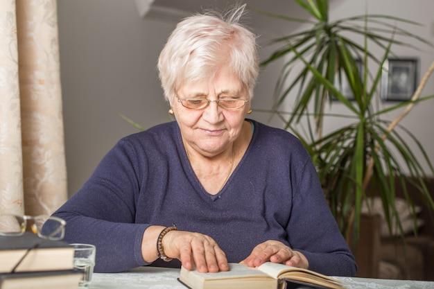 Senior Woman Lit Concentré Dans Un Livre Dans La Bibliothèque De La Maison De Retraite Photo Premium