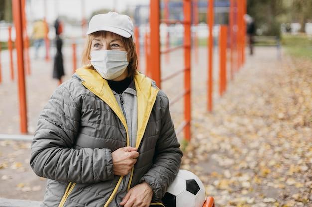 Senior Woman Avec Masque Médical Et Football à L'extérieur Photo gratuit