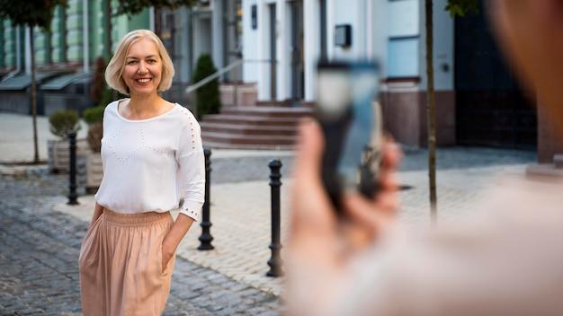 Senior Woman Photographié Par Partenaire Avec Smartphone à L'extérieur Photo Premium