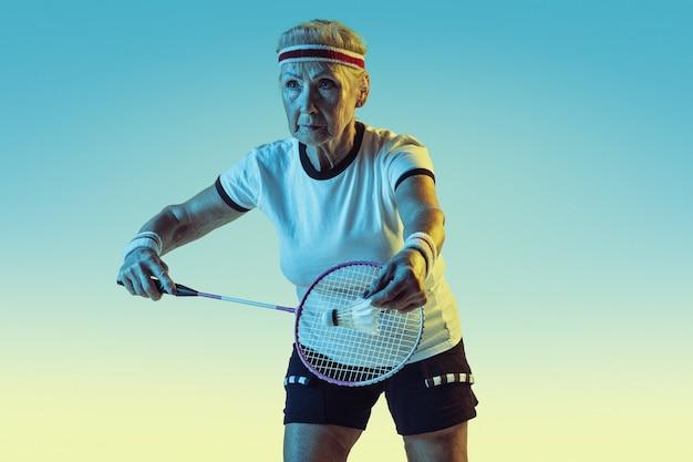 Senior Woman Playing Badminton En Vêtements De Sport Sur Un Mur Dégradé En Néon Photo gratuit