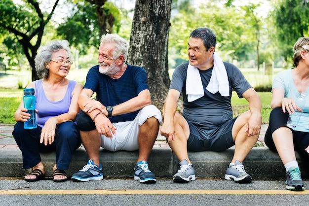 Seniors assis dans le parc après une séance d'entraînement Photo Premium