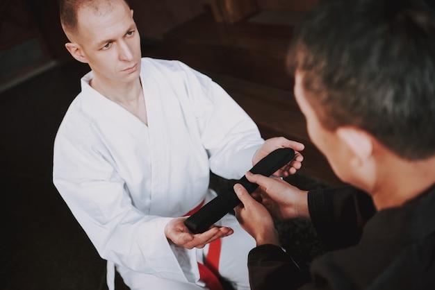 Sensei donne sa ceinture noire à un combattant d'arts martiaux Photo Premium