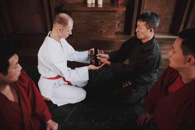 Sensei présente un combattant d'arts martiaux avec ceinture noire. Photo Premium