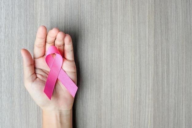 Sensibilisation au cancer du sein, main de femme tenant un ruban rose Photo Premium
