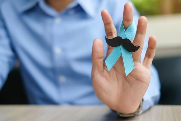 Sensibilisation au cancer de la prostate, main d'homme tenant un ruban bleu clair Photo Premium