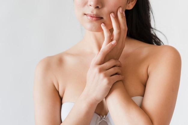 Sensuelle femme naturelle en soutien-gorge visage touchant Photo gratuit