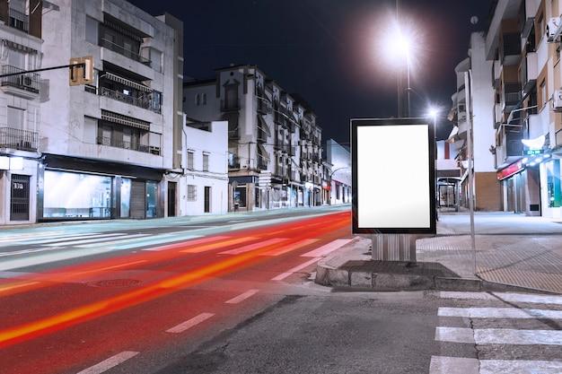 Sentiers de voitures passant près du panneau d'affichage vide sur le trottoir de la ville Photo gratuit
