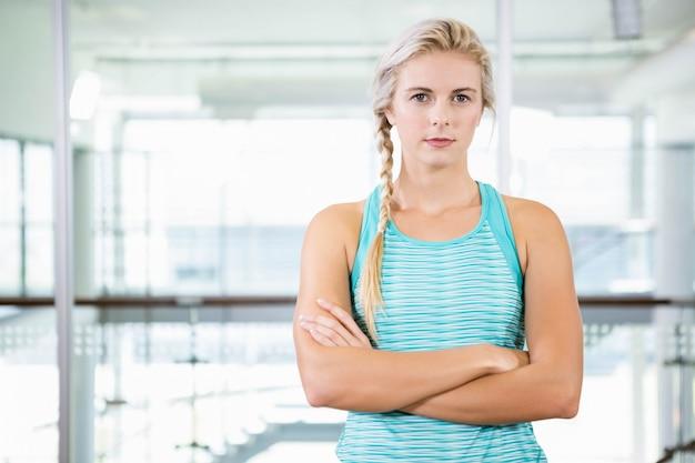 Sérieuse blonde debout avec les bras croisés au centre de loisirs Photo Premium