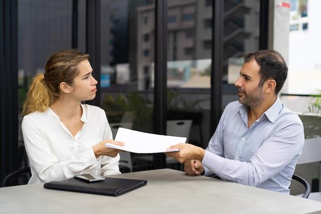 Sérieuse cliente donnant un document à un consultant financier Photo gratuit