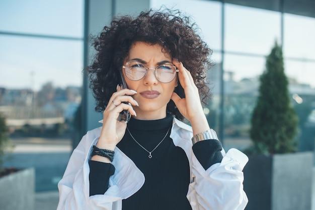 Sérieuse Femme De Race Blanche Aux Cheveux Bouclés Et Lunettes Regardant La Caméra Tout En Ayant Une Discussion Téléphonique D'affaires à L'extérieur Photo Premium