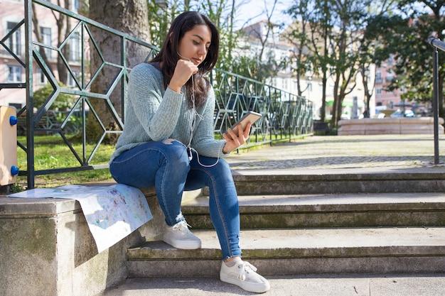 Sérieuse jolie femme écoutant de la musique sur le parapet des escaliers urbains Photo gratuit