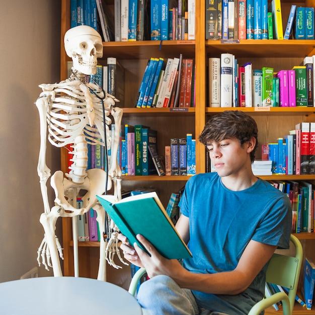 Sérieux adolescent lisant près de squelette Photo gratuit