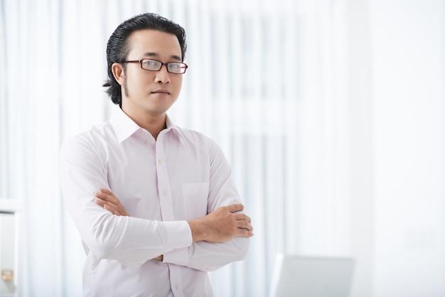 Sérieux homme d'affaires ethnique avec les bras croisés Photo gratuit