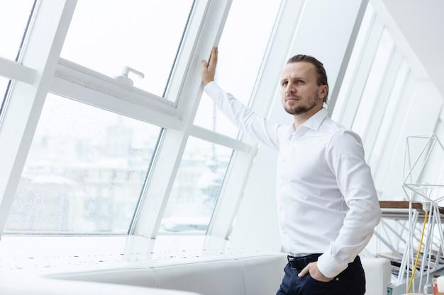 Sérieux homme barbu se pencha sur une fenêtre par ses mains debout dans l'intérieur moderne Photo Premium