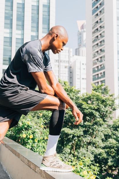Sérieux, jeune athlète africain, homme, debout, sur, toit, regarder bas Photo gratuit