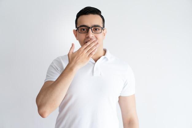 Sérieux jeune homme couvrant la bouche avec la main. mec attrayant gêné. Photo gratuit