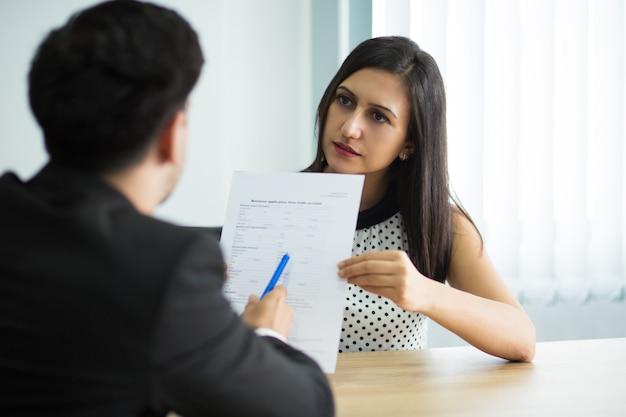 Sérieux jeune manager féminin montrant un contrat de partenariat Photo gratuit
