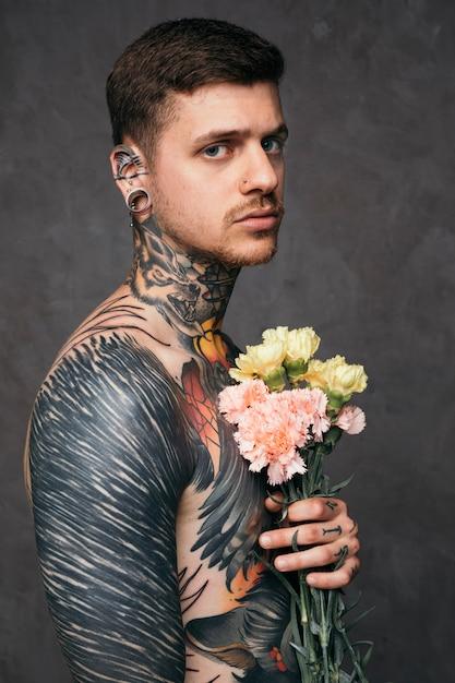 Sérieux, jeune, nez percé, oreilles, tenue, fleurs oeillet, main, debout, contre, toile de fond gris Photo gratuit