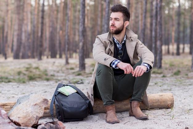 Sérieux jeune randonneur avec son sac à dos, assis sur un journal à la plage Photo gratuit