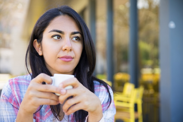 Sérieux jolie jeune femme profitant de boire du café au café Photo gratuit