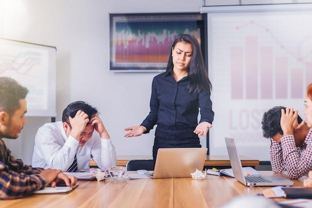 Sérieux patron femme grondant employé de l'équipe de marketing pour le résultat de la mauvaise affaire en réunion Photo Premium