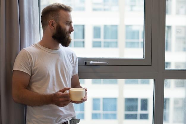 Sérieux songeur jeune homme barbu buvant du café Photo gratuit