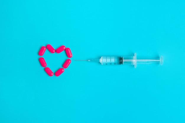 Une seringue tirée d'un médicament se trouve en face d'un cœur composé de pilules rouges se trouvant sur un fond bleu Photo Premium