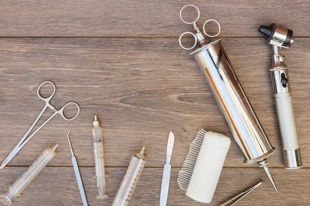 Seringue vintage en acier inoxydable; otoscope et équipement médical sur un bureau en bois Photo gratuit