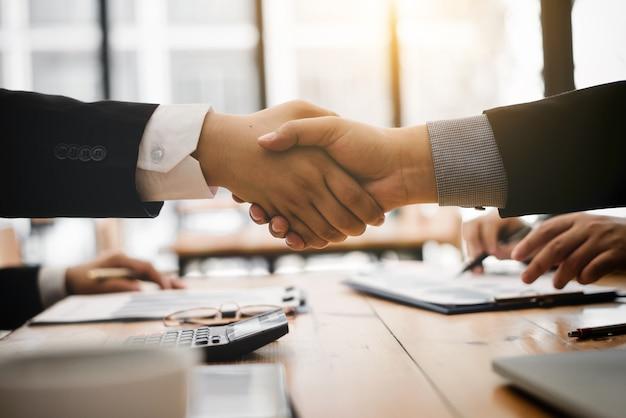 Serrer la main après avoir accepté de partenaire contractuel pour le produit d'importation. Photo Premium