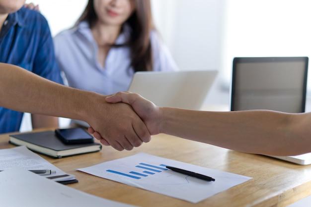 Serrer la main entre deux hommes d'affaires et une jeune femme les regardant et souriant. Photo Premium