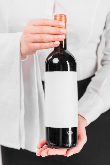 Servant montrant une bouteille de vin Photo gratuit