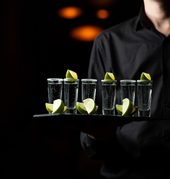 Servant tenant un plateau de service avec des cocktails au citron. Photo gratuit