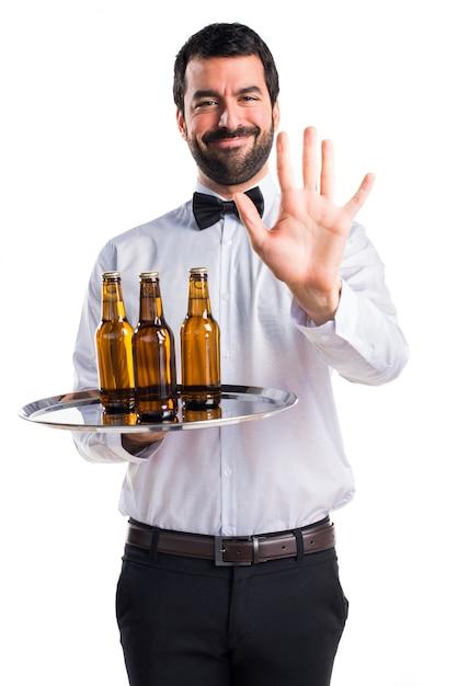 Serveur Avec Des Bouteilles De Bière Sur Le Plateau Comptant Cinq Photo gratuit