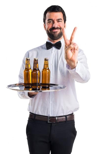 Serveur Avec Des Bouteilles De Bière Sur Le Plateau En Comptant Deux Photo gratuit
